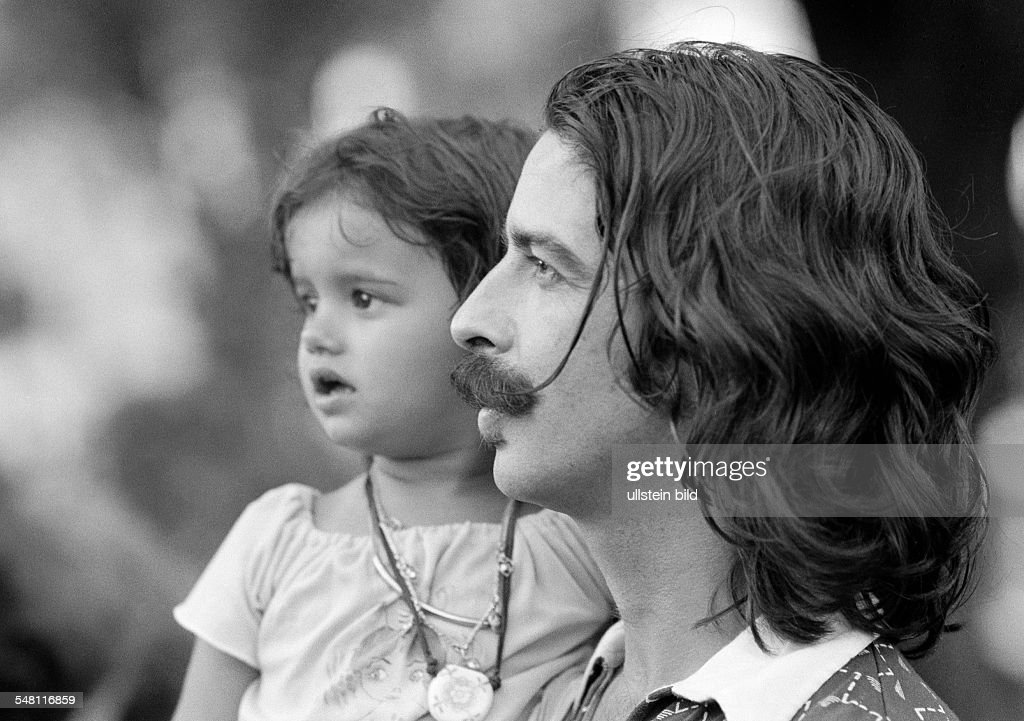 people, young father carries the little daughter in his arms, Brazilians, aged 25 to 35 years, aged 3 to 4 years, Brazil, Minas Gerais, Belo Horizonte - 31.01.1978 : News Photo