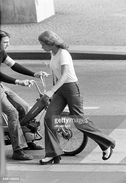 people young girl crosses the street young man driving a mofa TShirt trousers pullover jeans trousers aged 18 to 22 years