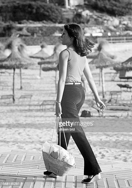 people young girl on shopping expedition on the beach shopping bag teeshirt trousers aged 18 to 22 years Spain Balearic Islands Majorca Palma de...
