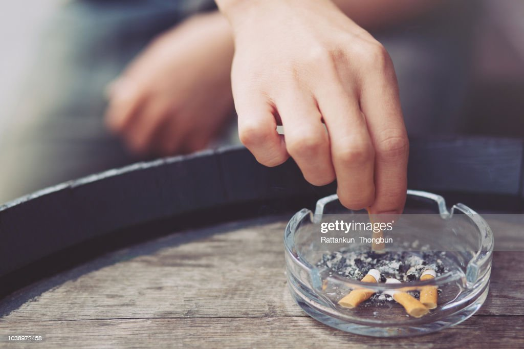 people young man hand putting out a tobacco cigarettes ashtray.,cigarette butt On a wooden bucket. : Stock Photo