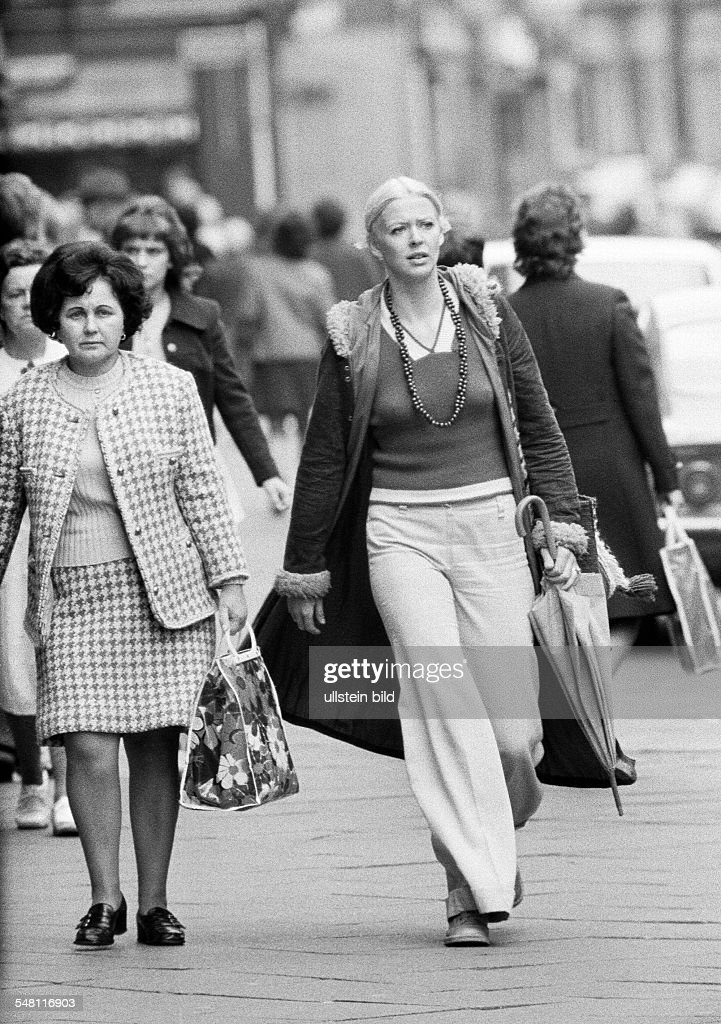 people, young woman, aged 30 to 40 years,woman, aged 40 to 50 years, pulli, jacket, trousers, female suit, stroll along the pedestrian zone, shopping, shopping bag, umbrella, freetime - 12.09.1972 : News Photo