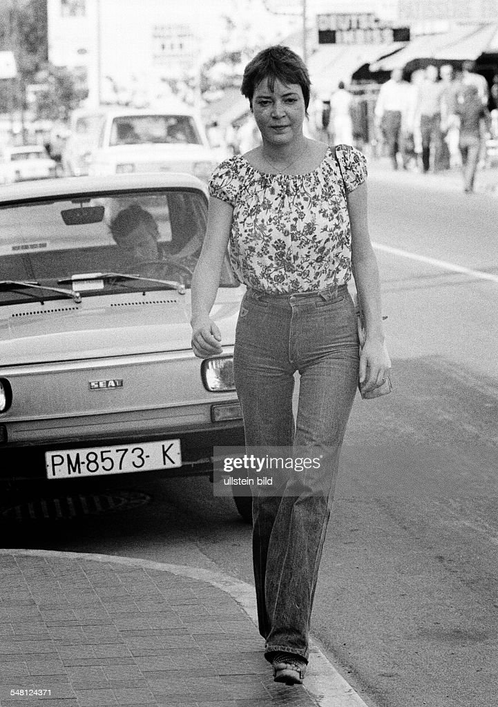 people, young woman on the pavement, blouse, jeans trousers, parking car, aged 22 to 28 years, Spain, Balearic Islands, Majorca, Palma de Majorca - 10.10.1978 : News Photo