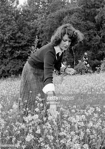 people young woman picks flowers in a flower meadow aged 25 to 30 years pulli skirt Betina