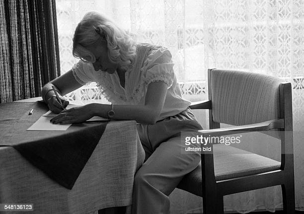 people young woman sits at a table writing a letter backlight twilight aged 25 to 35 years Elisabeth