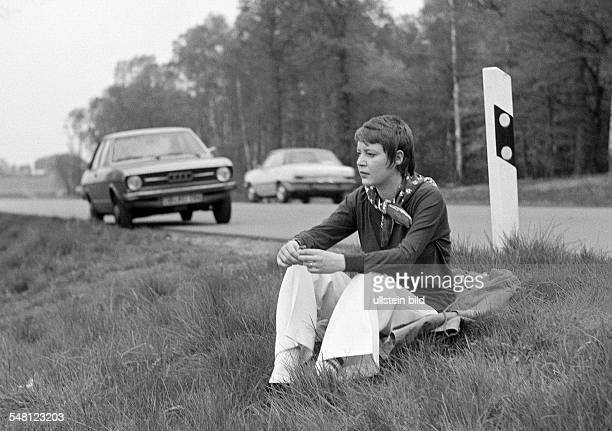 people young woman sitting at the roadside of a country road rest period in the background her parking car pulli trousers aged 25 to 30 years Monika