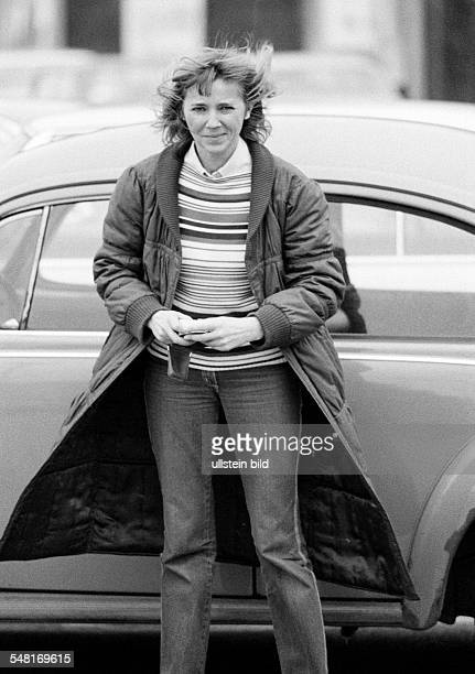 people young woman stands stands in front of a car pulli cloak jeans trousers aged 30 to 35 years Kriemhild