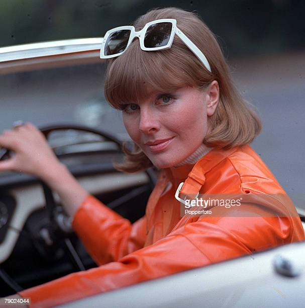 1967 People/Fashion A portrait of a woman wearing a fashionable orange PVC jacket and large sunglasses sitting in an open top sports car smiling at...