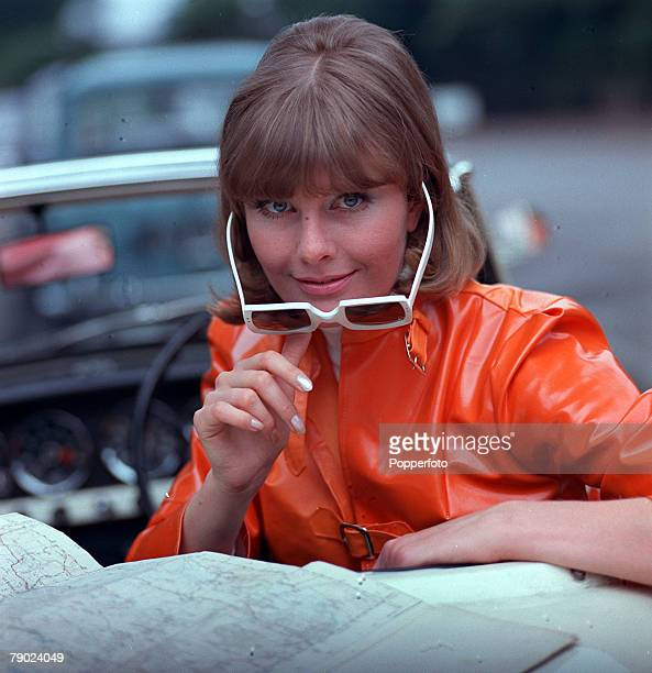1967 People/Fashion A portrait of a woman wearing a fashionable orange PVC jacket and large sunglasses which she is adjusting whilst sitting in an...
