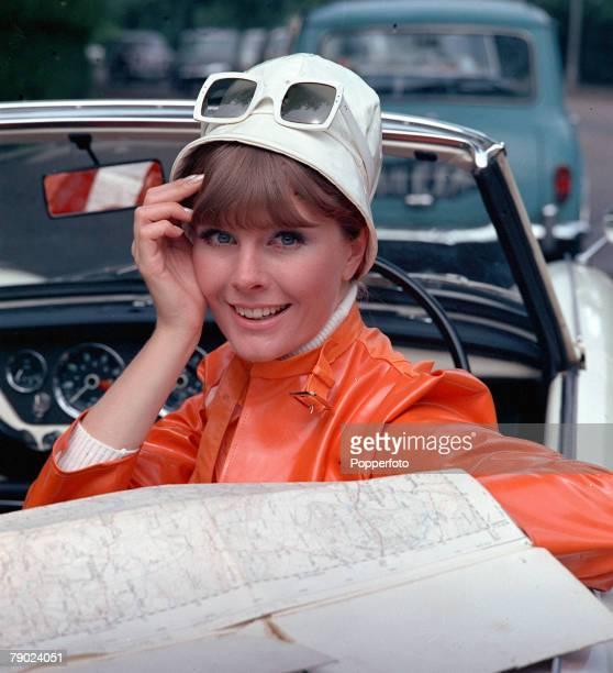 1967 People/Fashion A portrait of a woman wearing a fashionable orange PVC jacket white hat and large sunglasses whilst sitting in an open top sports...
