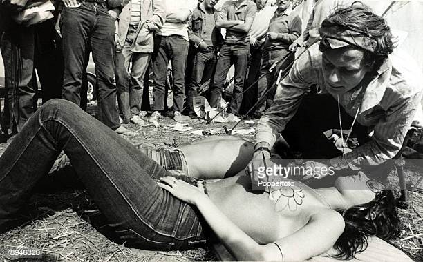 27th August 1970 A Belgian body artist at work decorating a topless woman with a flower design during the Isle of Wight Pop Festival