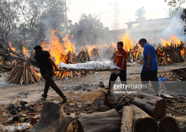 PeoplePeople carry the body of a person who died from the coronavirus disease , during a mass cremation, at a crematorium in New Delhi, India on...