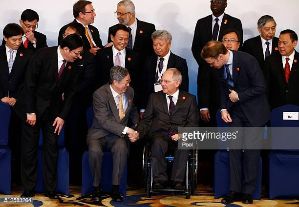 People's Bank of China Governor Zhou Xiaochuan greets German Finance Minister Wolfgang Schaeuble as Chinese Finance Minister Lou Jiwei and Chief of...