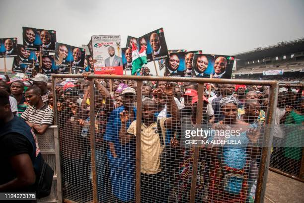 People's Democratic Party supporters hold cardboards bearing portraits of the PDP presidential candidate for the forthcoming elections in Nigeria...