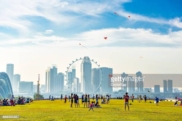 Singapore - August 14, 2016 : Peoples enjoy outdoor holiday activities at Singapore Marina Barrage Park with Singapore city background near Marina Bay