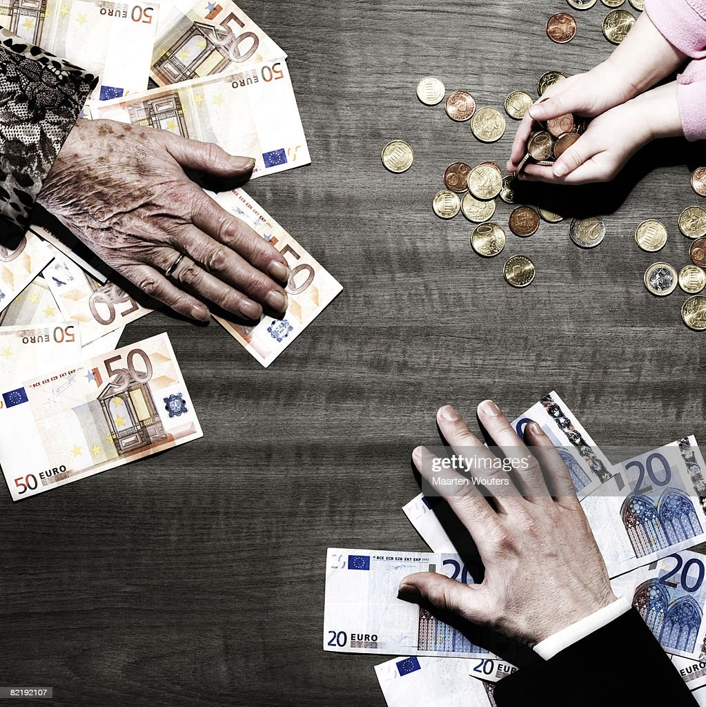 3 people's hands with money on table : Stock Photo
