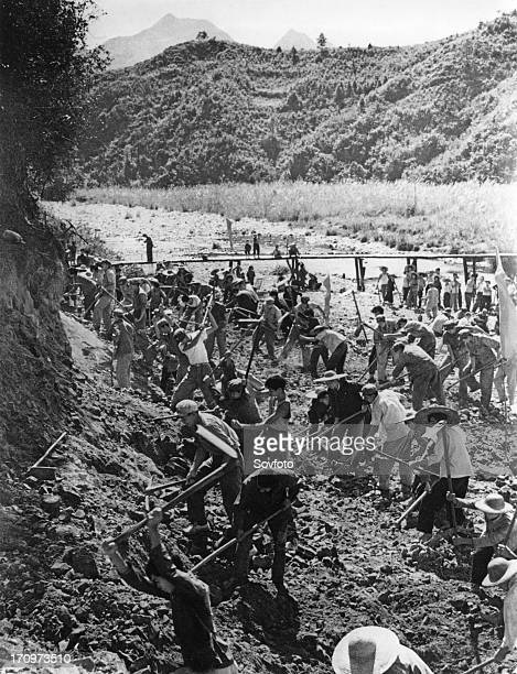 People's liberation army on a visit to the huangshantung brigade in kwangtung province work with commune members to dig a canal november 1968 china...