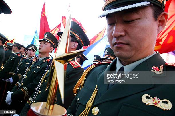 People's Liberation Army orchestra waits to perform to celebrate China's first manned spaceship on October 16, 2003 in Beijing, China. China launched...