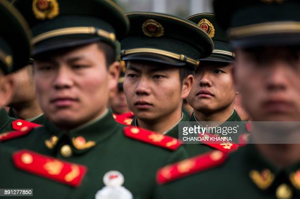 A People's Liberation Army soldier looks on as he participates in a ceremony at the Nanjing Massacre Memorial Hall on the second annual national day...