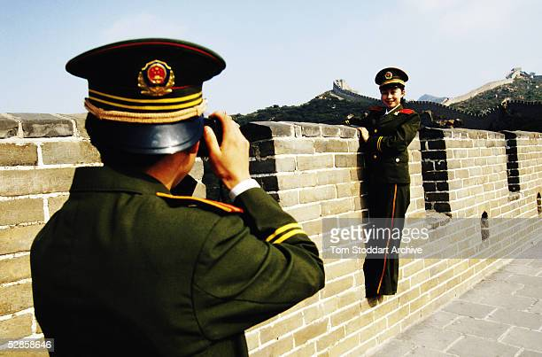 People's Liberation Army soldier photographs his girlfriend on the Great Wall of China