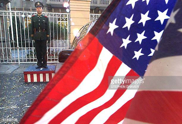 People's Liberation Army soldier stands guard in front of the US embassy in Beijing as an embassy car, flying the American flag , waits for US Trade...