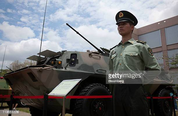 A People's Liberation Army soldier stands guard next to an armored personal carrier during the PLA Barracks Open day at Shek Kong Barracks in Hong...