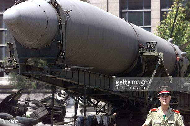 People's Liberation Army soldier stands in front of an old Chinese medium range ballistic missile 26 July 1999 on display in front of Beijing's...