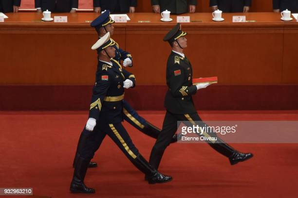 People's Liberation Army soldiers carry a copy of China's constitution as they prepare the oath ceremony after Presisdent Xi Jinping has been elected...