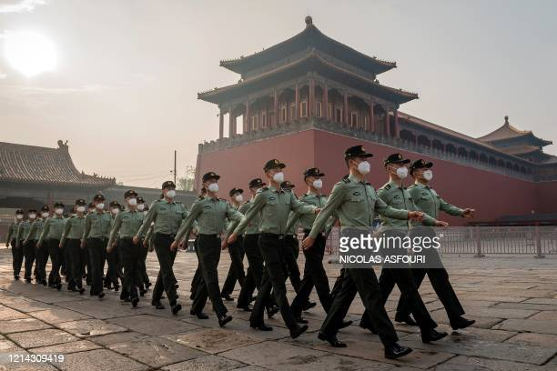 People's Liberation Army soldiers march next to the entrance to the Forbidden City during the opening ceremony of the Chinese People's Political...