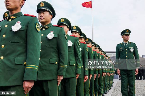 People's Liberation Army soldiers participate in a ceremony at the Nanjing Massacre Memorial Hall on the second annual national day of remembrance to...