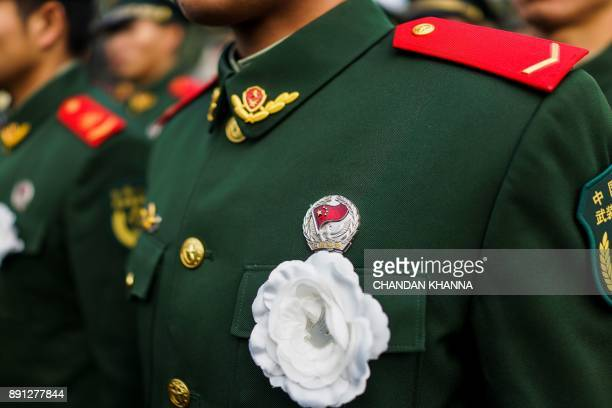 People's Liberation Army soldiers wears a flower as he participates in a memorial ceremony at the Nanjing Massacre Memorial Hall on the second annual...