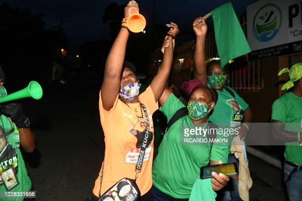 People's National Party and Jamaica Labour Party supporters react while they await the final count of votes for the St. Catherine north west...