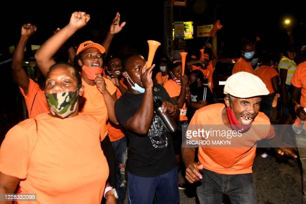 People's National Party supporters react while they await the final count of votes for the St. Catherine north west constituency during the general...