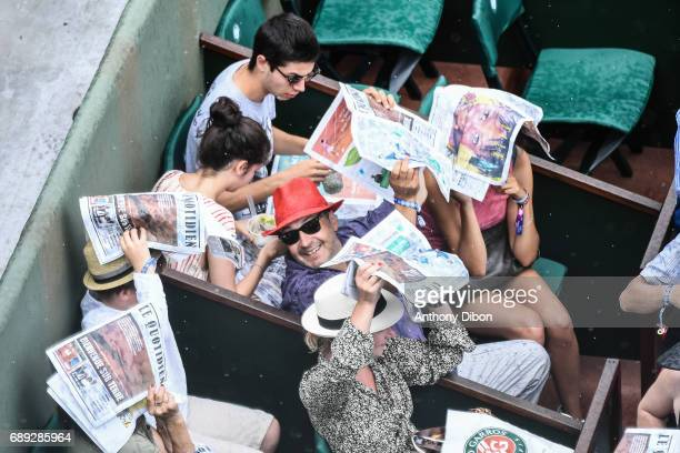 Peoples protects themself from rain with newspapers during first round on day 1 of the French Open at Roland Garros on May 28 2017 in Paris France