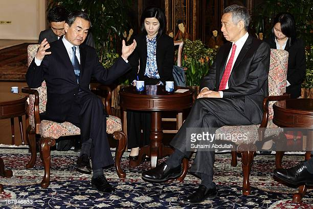 People's Republic of China Foreign Minister Wang Yi gestures as he speaks to Prime Minister of Singapore Lee Hsien Loong at the Istana during his...