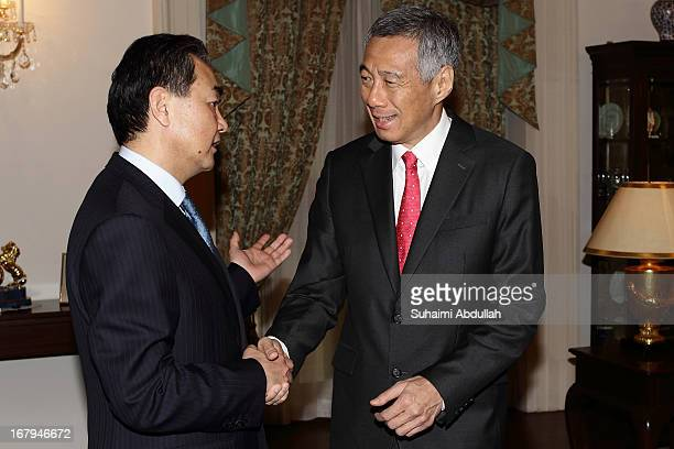 People's Republic of China Foreign Minister Wang Yi shakes hands with Prime Minister of Singapore Lee Hsien Loong at the Istana during his state...