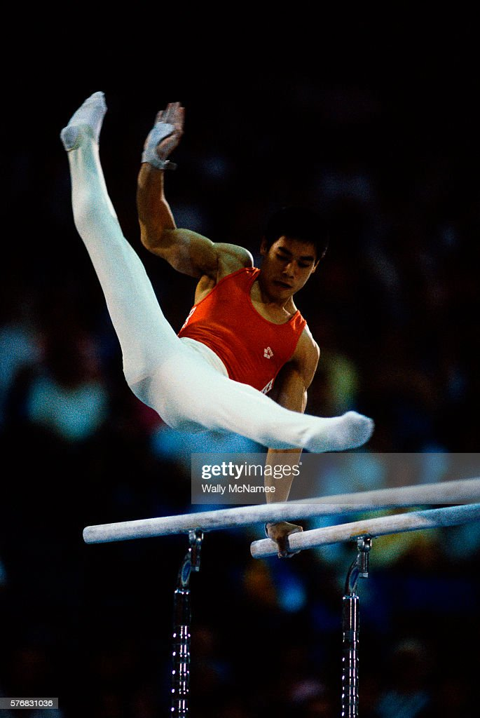 People's Republic of China star gymnist Ning Li careens above the parallel bars during team gymnastics competition at the 1984 Summer Olympic Games in Los Angeles.