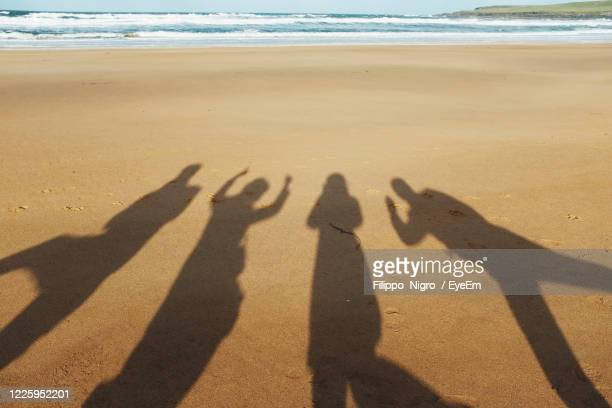 4 peoples shadow having fun - beach stock pictures, royalty-free photos & images