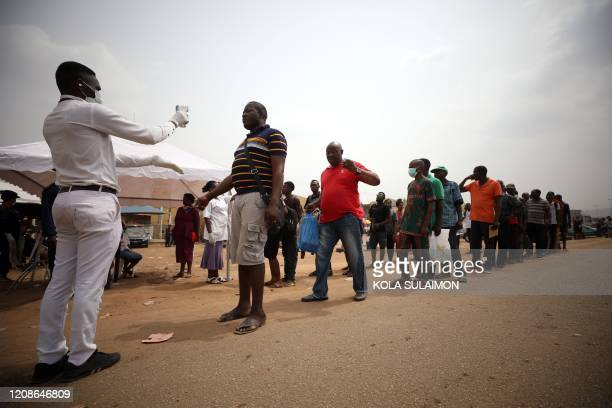 People's temperatures are measured at a border between Abuja and the Nasarawa State on March 30 as they leave to neighbouring states after Nigeria's...