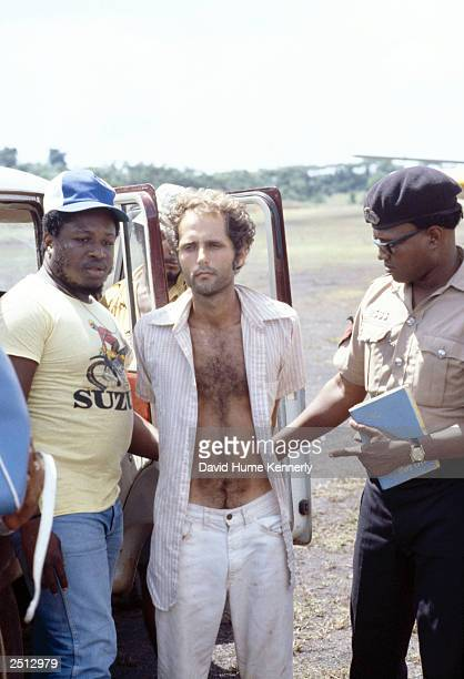 People's Temple follower Larry Layton stands with police following his arrest November 18 1978 in the shooting of two people on a remote Guyana...