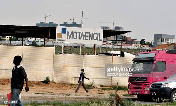 Peoplke walk past a construction site run by a Portugues construction company in Luanda on January 29, 2010. Portuguese, Chinese and Brazilian...