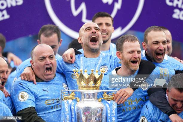 Pep Guardiola and his backroom staff celebrates with the Premier League Trophy as Manchester City are presented with the Trophy as they win the...