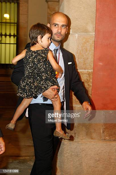 Pep Guardiola carrying daugther Valentina is shown after receiving a gold medal of honour as a recognition for his career and his contribution to the...