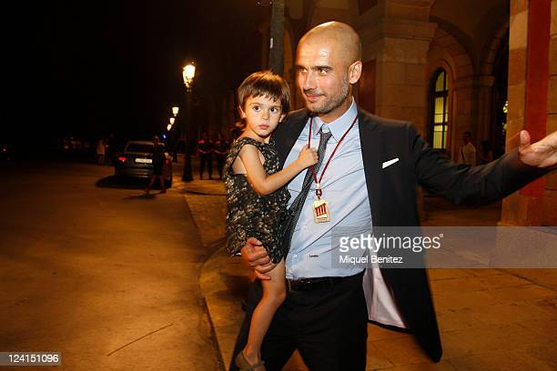 Pep Guardiola carrying his daugther Valentina is shown after receiving a gold medal of honour as a recognition for his career and his contribution to...