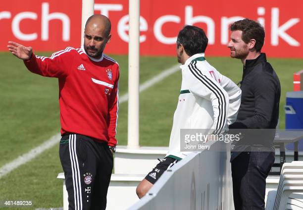 Pep Guardiola, coach of Bayern talks with his fitness coach Lorenzo Buenaventura and former Tottenham coach Andre Villas-Boas at the end of practice...