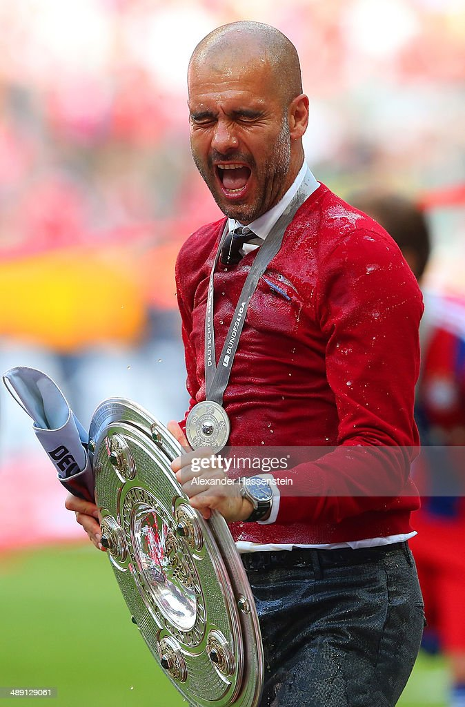 Pep Guardiola head coach of Bayern Muenchen celebrates with the Bundesliga championship trophy as he is soaked after the Bundesliga match between Bayern Muenchen and VfB Stuttgart at Allianz Arena on May 10, 2014 in Munich, Germany.