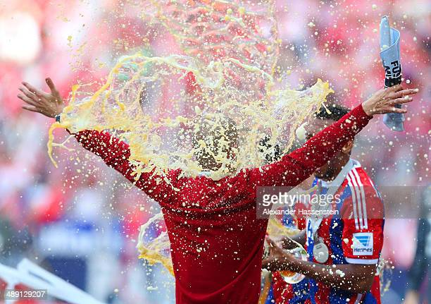 Pep Guardiola head coach of Bayern Muenchen is showered with beer as he celebrates the Bundesliga championship after the Bundesliga match between...