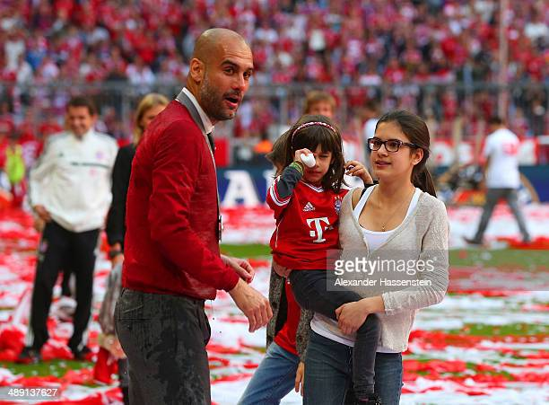 Pep Guardiola head coach of Bayern Muenchen talks to his daughters Maria Guardiola and Valentina Guardiola after the Bundesliga match between Bayern...