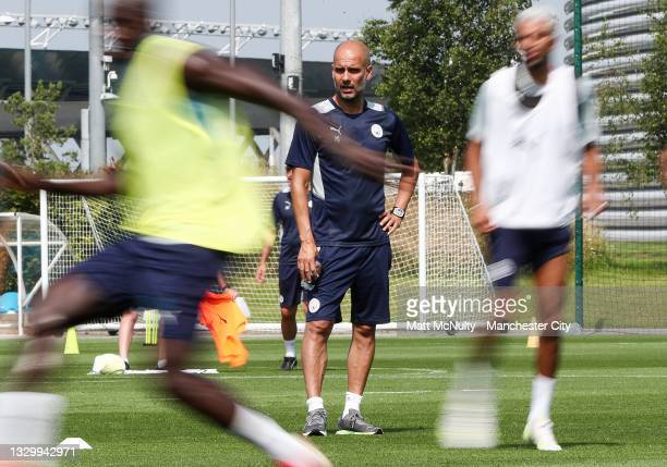 Pep Guardiola, maanger of Manchester City watches his players during a training session at Manchester City Football Academy on July 20, 2021 in...