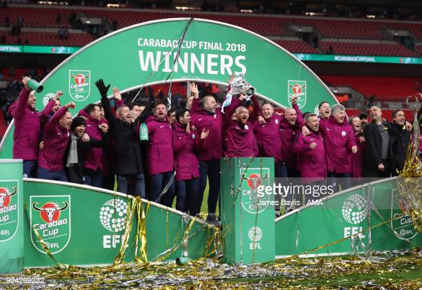Pep Guardiola manager / head coach of Manchester City celebrates with his coaching staff after winning the Carabao Cup after the Carabao Cup Final...