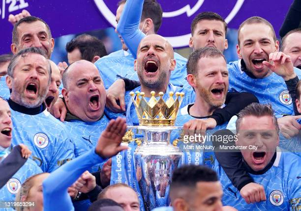 Pep Guardiola, Manager of Manchester City and members of backroom staff celebrate with the Premier League Trophy as Manchester City are presented...